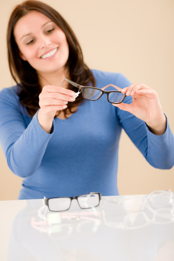 Woman looking at her glasses